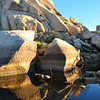 Where the boulders kiss the water at Barker Dam in Joshua Tree National Park