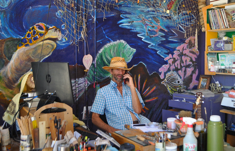 Doug Whitfield, owner of 29 Palms Creative Center with Wife Gretchen, answers the phone amidst his art paradise
