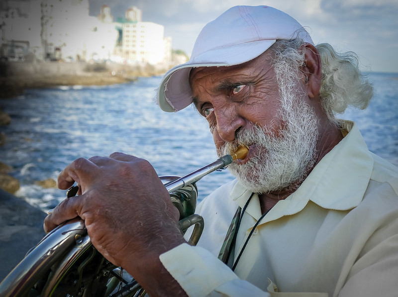 Cuban with French horn on the Malecón - Havana's pedestrian waterfront seawall.