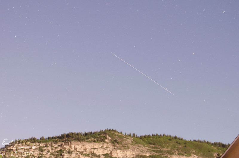 This is a 30 seconds exposure of the International Space Station flying overhead.  That is Bald Mountain on the lower part of the picture.  The specks in the sky are stars.  <br /> <br /> It looks like daylight, but it's actually 11:00pm.