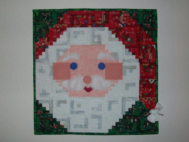 "2012 - Santa<br /> 18"" x 18""<br /> Reprise of previously made hanging, this one for me."