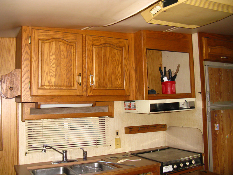 Whatever was above the cook top is missing.  That compartment has a roof vent, so it was probably a microwave/convection oven combo.  The left hinge on the cook top cover is missing.  The door panels on the refrigerator are badly scratched up and still have some stickers glued to them.