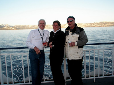 Kevin, Lori from Boston, and Tom from Kensington, Maryland stand on the deck of the Tahoe Queen paddlewheeler on Lake Tahoe at dusk