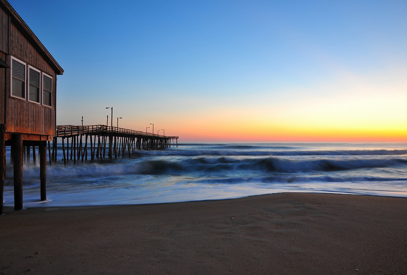 Waves rolling in from the sunrise at Nags Head Pier, Outer Banks NC