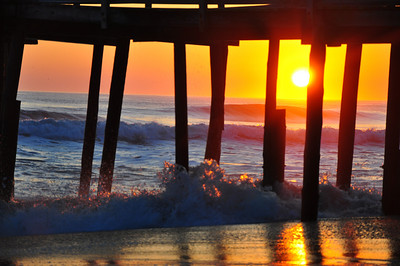 Sunrise under the Nags Head Pier, lighting the rolling surf on fire.