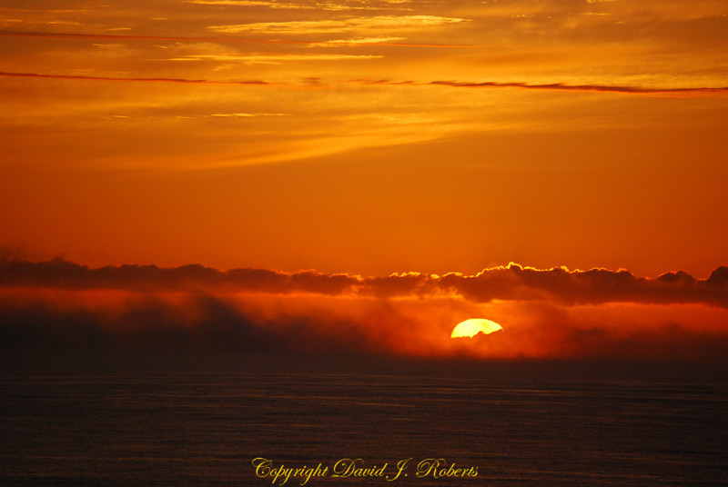 The sun just peeks over the clouds as it says goodbye for the day at Patrick's Point State Park, California