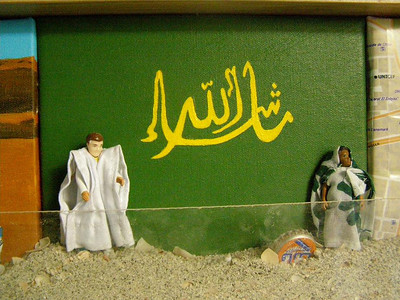 """Mauritania Tableau, 2: In front of  the word """"Masha'allah"""" (Arabic for """"All is as Allah wants it to be"""") stand a man dressed in a boubou and a woman in a moulafa. (acrylic on canvas, plastic figures in cloth garments)"""