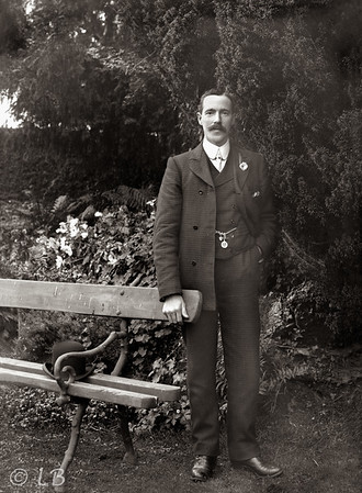 RC McKane, photographer standing by bench