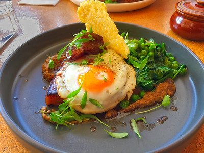Bacon steak, fried egg with beans and peas