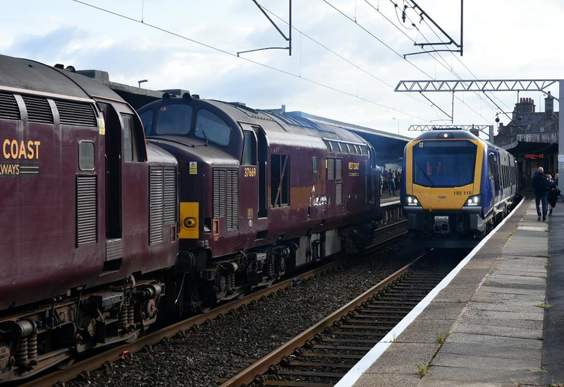 37669+ 37685 Loch Arkaig (5Z25) & 195116 Proud to be Northern (5J88), Carnforth, Thurs 18 July 2019 - 0752.  The Scarborough Spa stock enters the platform having been held for Northern's delayed 1C50 0522 Manchester Airport - Barrow.  The 195 waits to run empty to Newton Heath.