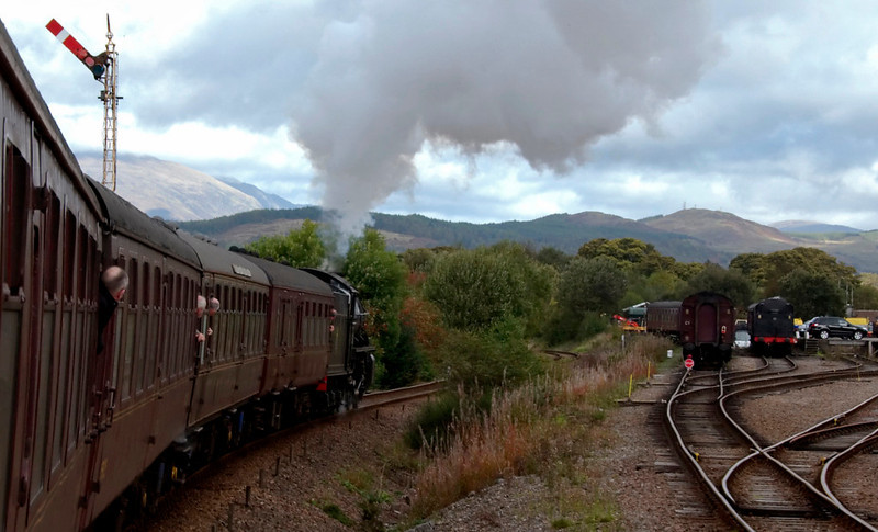 62005 Lord of the Isles, 1Z25, passing Fort William yard, 26 September 2009 - 1328     Visible at right is the ECS for the 'Jacobite' summer steam train to Mallaig.  It was not in use as the 'Jacobite' does not run at weekends as the season winds down.  Also visible is the tender of 45407, which shared 'Jacobite' duties with 62005.  The two locos worked alternate weeks.  The K1 spent the entire May - October 'Jacobite' season at Fort William, but the Black 5 had replaced sister 45231 at the beginning of August.  Steam trains have been running to Mallaig since 1984.
