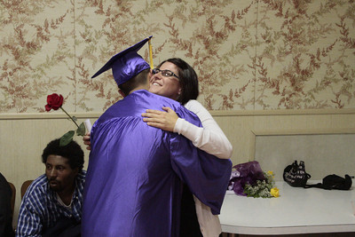 Shaun Walker/The Times-Standard  Student Gerardo Cortez hugs teacher Randi Golat after giving her a rose at Alder Grove Charter School's high school graduation ceremonies at Humboldt Grange on Thursday afternoon. Fifteen students received diplomas, and earlier other students graduated from the school's middle school program.