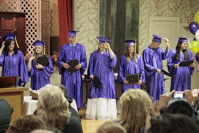 Shaun Walker/The Times-Standard  Students switch their tassels during Alder Grove Charter School's high school graduation ceremonies at Humboldt Grange on Thursday afternoon. Fifteen students received diplomas, and earlier other students graduated from the school's middle school program.
