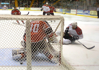 Adirondack's Harry Zolnierczyk falls to the ice as his shot on goal scores past Portland Pirate goalie Chad Johnson during Adirondack's home opener Saturday in Glens Falls. Ed Burke 10/13/12