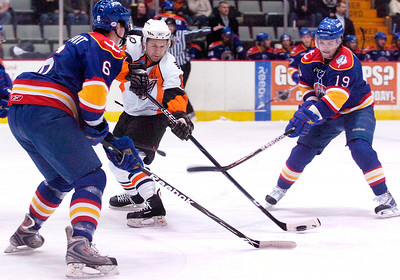 Jon Matsumoto, Phantoms, carries the puck down the rink against the Norfolk Admirals Ty Wishart, left, and slashing sticks by Justin Keller during their first hockey game of the new year Saturday evening. Photo Erica Miller 1/2/10 spt_Phantoms4_Sun