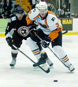 Joey Mormina, Adirondack Phantoms, brings the puck down the rank against Dustin Jeffrey, Wilkes-Barre/Scranton Penguins, during their hockey game Sunday afternoon at the Glens Falls Civic Center. Photo Erica Miller 2/14/10 spt_Phantoms1_Mon