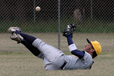 Josh Jackson/The Times-Standard  Del Norte's #17 tumbles in the outfield during Saturday's game in McKinleyville.