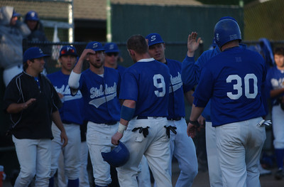 The Humboldt Steelheads' XX Morgan and Eric Heckman, right, are congratulated by teammates after scoring on Dave Grytness' RBI-double in the X inning against the Sluggers.