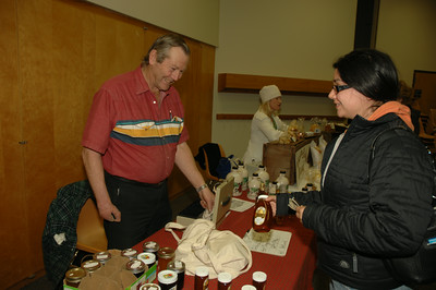 Kristin Robinson of Ballston Spa buys some honey from Richard Stutzenstein of Greenfield Center. photo by Tony Bucca