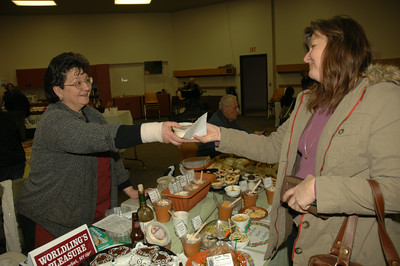 Linda Gross (right) recieves a container of gourmet dip from Heidi Flynn of Worldling's Pleasure of Watervliet. photo by Tony Bucca