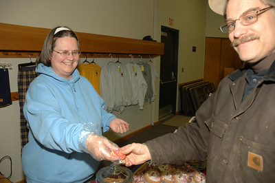 Rob Pastore buys a cookie from Lynette Janssen of Aunt Nette's Sweets of Burnt Hills. photo by Tony Bucca