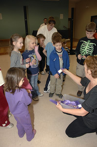 Meg Stevens hands out ribbons of Participation to the kids at the Milton Community Center. photo by Tony Bucca