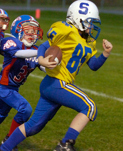 Saratoga Pop Warner's Logan Harris carries the ball as South Glens Falls' Nate Angell pursues during Saturday's Mighty Mite division game at East Side Rec Field. Ed Burke 10/10/09