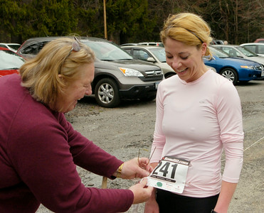 Stephanie Casey of Saratoga Springs turns in her tag to race volunteer Nancy O'Leary after being the first female finisher in the St. Peter's Keys 10K Saturday at Saratoga Spa State Park. Ed Burke 4/18/09