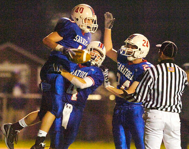 Jon Noonan leaps into the arms of Joey Moore and high fives James  Millar after catching the football in the ends zone during their game against New Rochelle Saturday evening in Kingston. Photo Erica Miller 11/21/09 news_togaFootball1_Sun