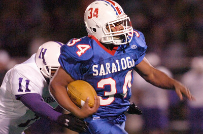 Tony DeLoatch, Saratoga, runs down the sideline with the football as Charles Larrier, New Rochelle, shortly behind during their game Saturday evening in Kingston. Photo Erica Miler 11/21/09 spt_TogaRoch1_Sun