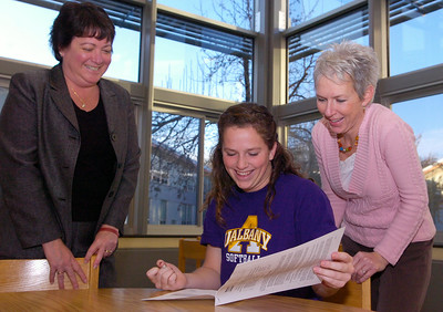 Senior at BH-BL Emily Ostrom glances over the paper worked signed for University of Albany softball team with her mother Peggy (behind) and Principle Mary Ellen Symer in the High Schools Library Monday afternoon. Photo Erica Miller 11/16/09 spt_EmilyOstrom_Tues