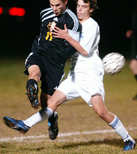 Jon Marra of Ballston Spa kicks the ball past Saratoga's Steve Celeste of their co-championship section 2 Class AA soccer game Wednesday evening in Colonie. Photo Erica Miller 11/10/10 bspa_CoChamps2
