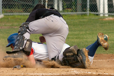 Saratoga's Erich Lange tries to tunnel under Amsterdam catcher Sean Whitty after getting caught off base during Friday's game in Queensbury. Lange was out on the play. Ed Burke 5/29/09
