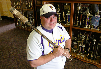 Saratoga Central Catholic baseball coach Alphonse Lambert Jr. shoulders a bat his father gave him when he started coaching. Ed Burke 7/14/09