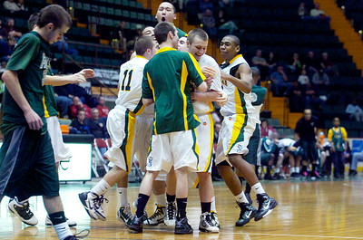 Coleman Catholic High School's teammates gather in joy around Thomas Murphy made the winning free-throw shot winning their basketball game against Finney High School Friday afternoon at the Glens Falls Civic Center. Photo Erica Miller 3/18/11 spt_Coleman6