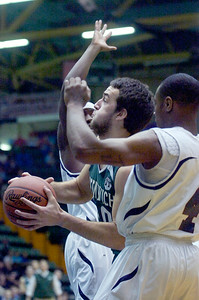 Greenwich's Ryan McFee plows through Syracuse Academy of Science's Jamon Haddon (closest) and DeOndray Tape during their Class C semi-final basketball game Friday afternoon at the Glens Falls Civic Center. Photo Erica Miller 3/18/11 spt_Greenwich2_Sat