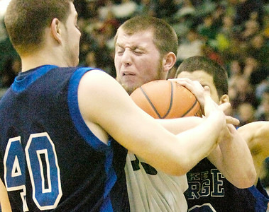 Greenwich's Jason Flynn covers up the ball while pressured by Lake George's J.D. Jenkins (40) and Jeff Maldonado. Ed Burke 3/5/11