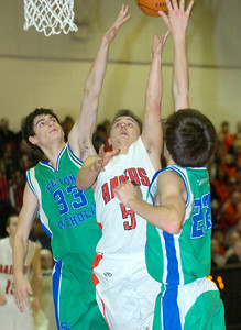 Mechanicville's Sam DeCelle drives between Seton Catholic defenders Carson Hynes (33) and Carlos Alvarez during Wednesday's CLass C regional playoff win at Stillwater High School. Ed Burke 3/7/12