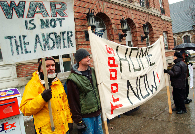 Left, Bill Pearson of Brattleboro and William Woods of Westminster, stand in front of the post office on Main Street in Brattleboro with fellow anti war protestors, Wednesday afternoon.<br /> (Zachary P. Stephens/Reformer)
