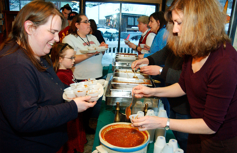 Right, Laurie Krualt, a Winter Carnival comittee member, serves chili to Gail Maken of Brookline, at the Marina in Brattleboro, Wednesday evening during the Winter Carnival Chili Cookoff.<br /> (Zachary P. Stephens/Reformer)
