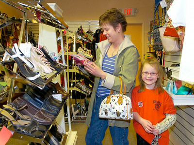 Nursing a broken arm, six year old Holly Deyoe and her mother Amberlyn Deyoe of Schuylerville shop for shoes Thursday at Treasures Consignment Boutique and Thrift Shop at 60 West Ave. The recently opened business is operated by the Saratoga Hospital Volunteer Guild. Ed Burke 4/30/09