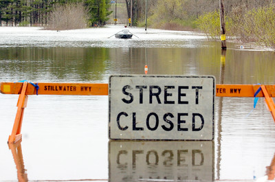 A man rows his way down the street as it is over flooded from the Hudson River on Wrights Loop in Stillwater  as the Hudson River rose to rapid heights as flooding occurred for the second day. Photo Erica Miller 4/29/11 news_Flooding8_Sat