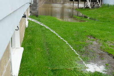 Water pours out of someone's home on Route Route 4 in Schuylerville where the entire park is completely submerged underwater as flooding occurring on the Hudson River. Photo Erica Miller 4/29/11 news_Flooding3_Sat