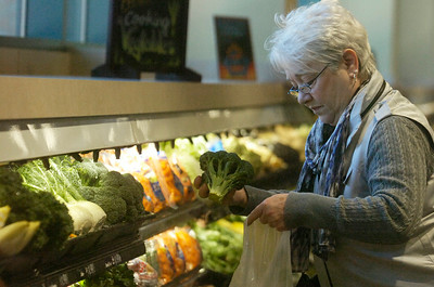 At the new Price Chopper located at The Market Center customer Suzanne Cleary grabbed fresh broccoli from the large array of vegetables on their soft opening day in their new location on Sunday, the entire place was stocked and cleaned since Monday. Photo Erica Miller 4/29/12 news_PriceChopper4_Mon