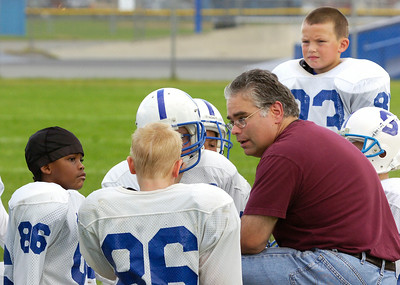 Head coach Matt Riker talks to his team mates during their half-time against the Troy Patriots for the 7,8,9 year old Might Mites game Sunday morning at the East Side Rec. Photo Erica Miller 8/30/09 spt_PopWarner5_Mon