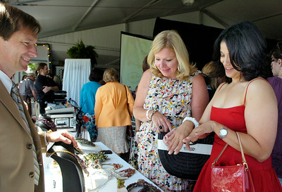 Maureen Bennett (back), of Voorheesville,  and Lena Hart, of Albany, glance at some of Peter Ciesla's jewelry (left) during the fashion show  put on my Saratoga Truck in benefit for the Ronald McDonald House Charities, held at the Saratoga Race Course Rail Pavilion Thursday morning. Photo Erica Miller 8/27/09 fea_Fashion3_Fri