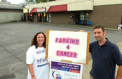 Mary Jo Duval Nilsson and Peter Nilsson set up to park cars at Caroline and Henry Streets to help raise money for cancer research.  Ed Burke 8/28/09
