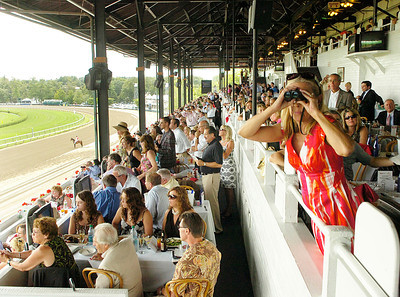 Peg Schumacher of Slingerlands uses binoculars to get a better look at race 7 on the inner turf.  Schumacher has attended Travers Day for over 25 years. Ed Burke 8/27/11