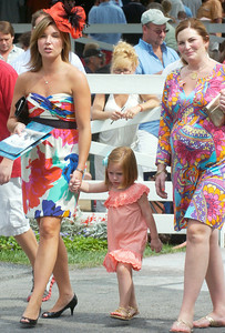 Entering the paddock Saturday, Abby Castellano, left, wife of Travers-winning jockey Javier Castellano holds the hand of three year old Ava Brown, daughter of trainer Chad Brown and his wife Terrill Brown at right. Ed Burke 8/27/11