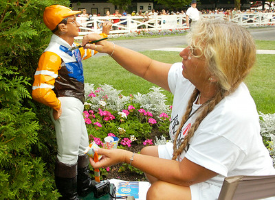 Robin Schumacher  of Porter Corners paints the paddock jockey with Travers-winning owner Mike Repole's colors after Saturday's race. Painting the jockey immediately after the race in a Travers' tradition. Ed Burke 8/27/11